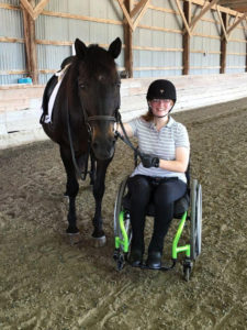 para-dressage student in wheelchair next to her horse