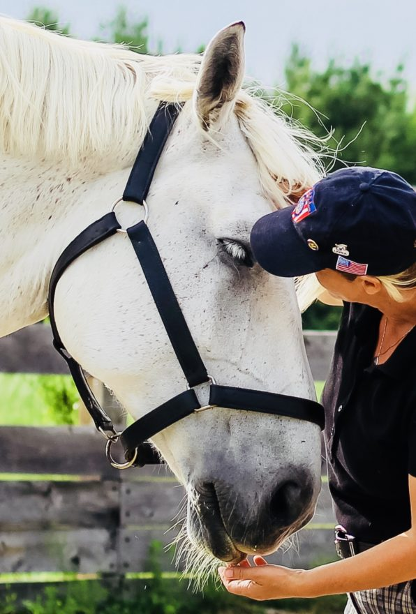 Photo of Sarah sharing a tender moment with a horse.