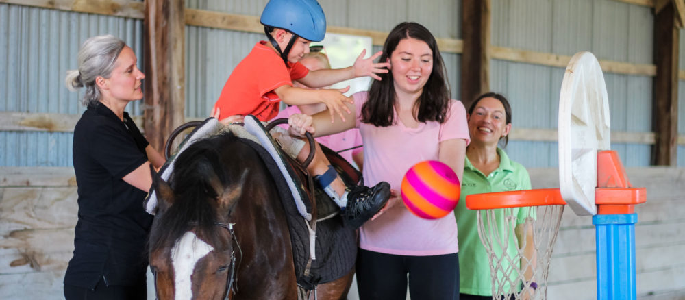 Photo of a therapy student throwing a ball into a hoop while on horse back.